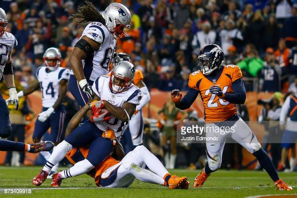 Running back Dion Lewis of the New England Patriots works for a third quarter rushing touchdown against the Denver Broncos at Sports Authority Field...