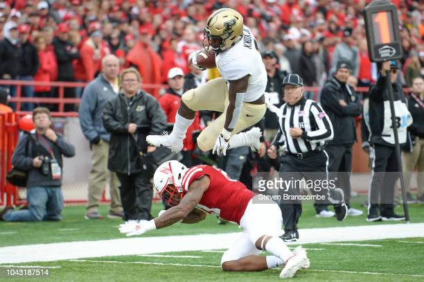 Running back DJ Knox of the Purdue Boilermakers leaps over the tackle attempt of defensive back Lamar Jackson of the Nebraska Cornhuskers in the...