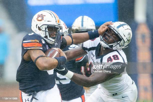 Running back D.J. Williams of the Auburn Tigers stiff arms linebacker Jaleel Laguins of the Samford Bulldogs during the second quarter at Jordan-Hare...