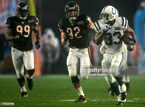 Running back Dominic Rhodes of the Indianapolis Colts carries the ball 36yards past Tank Johnson and Hunter Hillenmeyer of the Chicago Bears during...