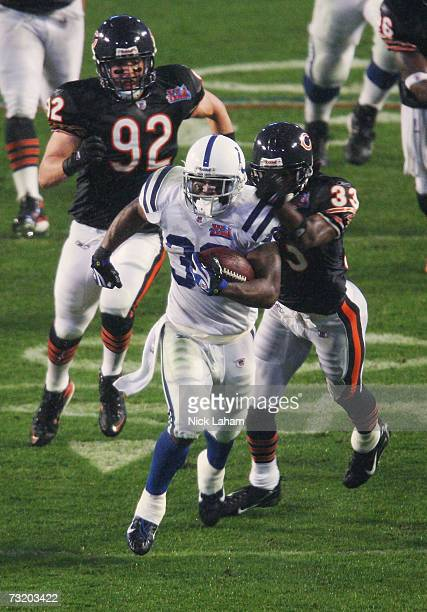 Running back Dominic Rhodes of the Indianapolis Colts runs past Charles Tillman and Hunter Hillenmeyer of the Chicago Bears on a 36yard carry in the...