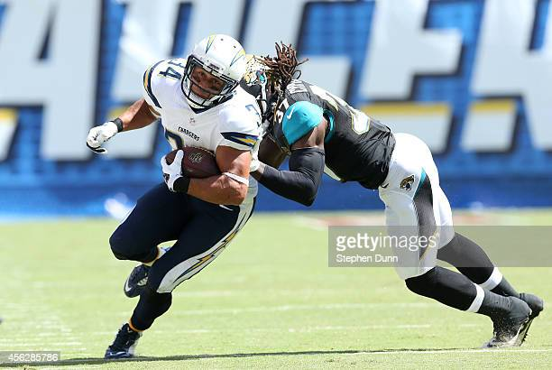 Running back Donald Brown of the San Diego Chargers carries the ball against safety Johnathan Cyprien of the Jacksonville Jaguars at Qualcomm Stadium...