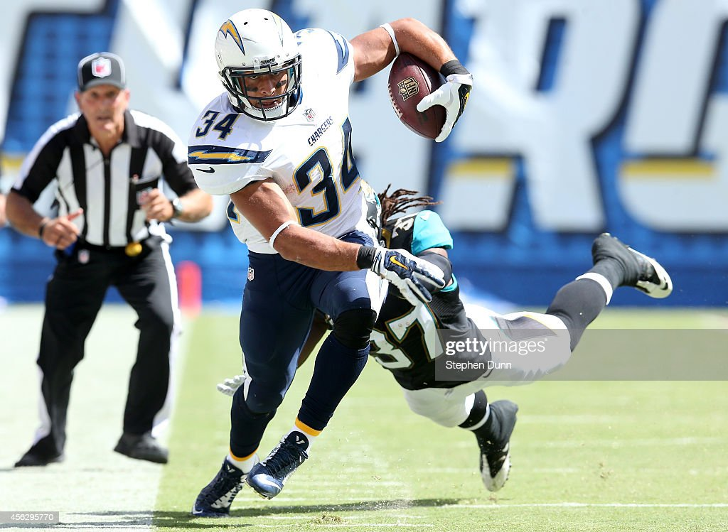 Running back Donald Brown #34 of the San Diego Chargers carries the ball against safety Johnathan Cyprien #37 of the Jacksonville Jaguars at Qualcomm Stadium on September 28, 2014 in San Diego, California.