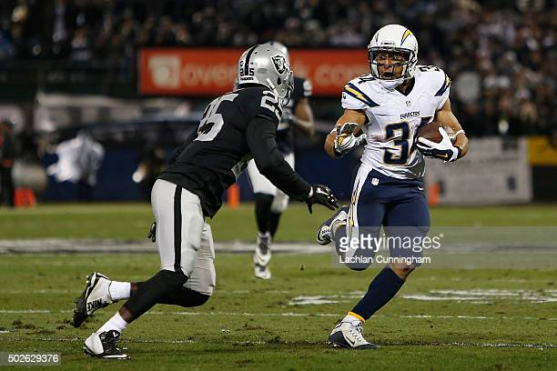 Running back Donald Brown of the San Diego Chargers looks to evade cornerback DJ Hayden of the Oakland Raiders in the first quarter at O.co Coliseum...