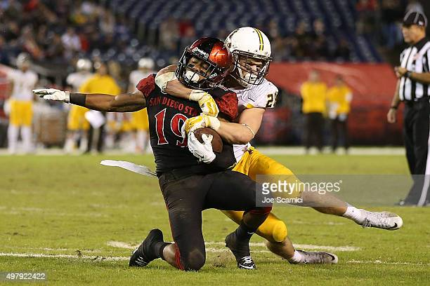 Running back Donnel Pumphrey of the San Diego State Aztecs is taken down by safety Andrew Wingard of the Wyoming Cowboys in the third quarter at...