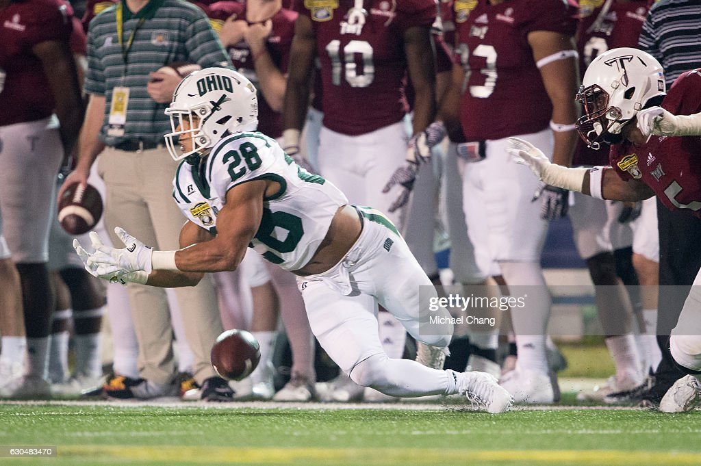 Running back Dorian Brown #28 of the Ohio Bobcats attempts to catch a pass in front of defensive end Sam Lebbie #5 of the Troy Trojans on December 23, 2016 in Mobile, Alabama. The Troy Trojans defeated the Ohio Bobcats 28-23.