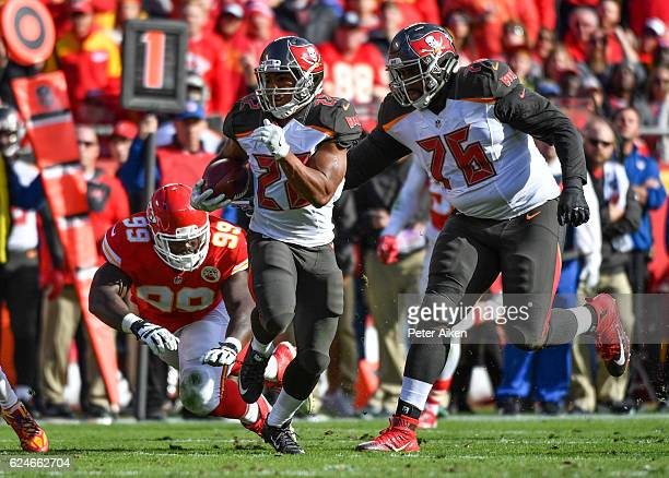 Running back Doug Martin of the Tampa Bay Buccaneers avoids the tackle attempt of defensive tackle Rakeem NunezRoches of the Kansas City Chiefs at...
