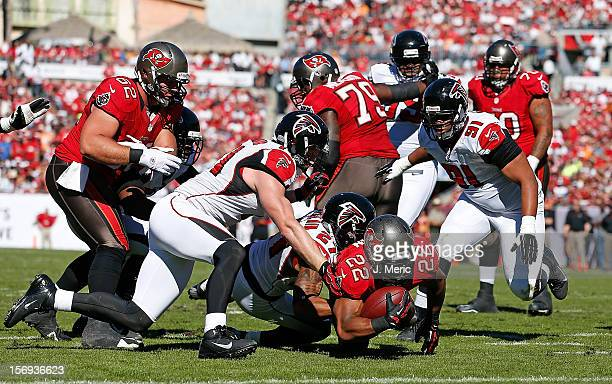 Running back Doug Martin of the Tampa Bay Buccaneers dives for extra yardage as defender Robert McClain of the Atlanta Falcons brings him down during...