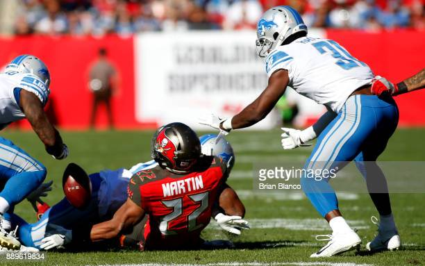 Running back Doug Martin of the Tampa Bay Buccaneers fumbles the ball allowing it to be recovered by defensive back DJ Hayden of the Detroit Lions...