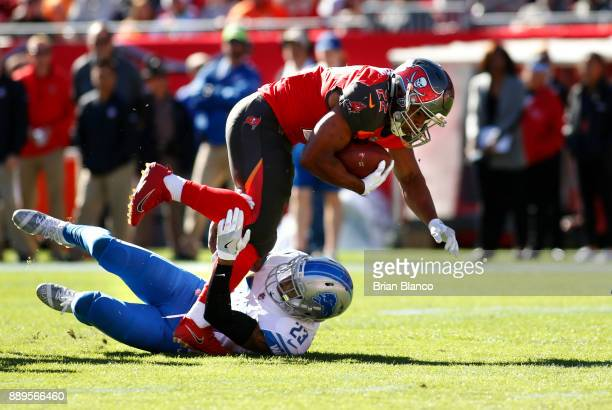 Running back Doug Martin of the Tampa Bay Buccaneers is stopped by cornerback Darius Slay of the Detroit Lions after hauling in a 12yard pass from...