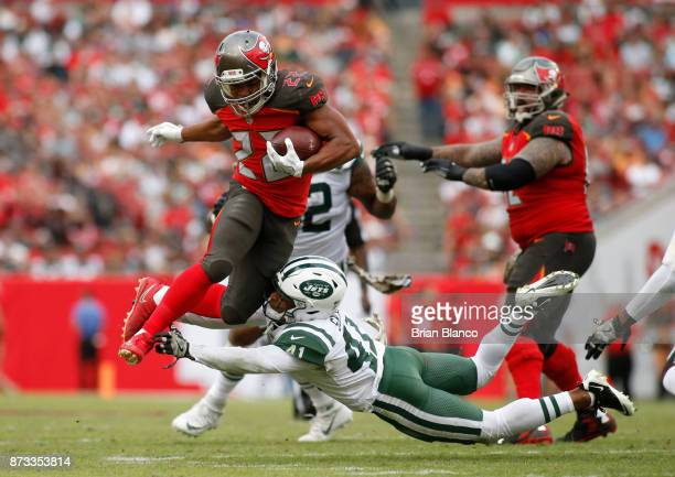 Running back Doug Martin of the Tampa Bay Buccaneers leaps over an tackle attempt by cornerback Buster Skrine of the New York Jets as he runs for a...