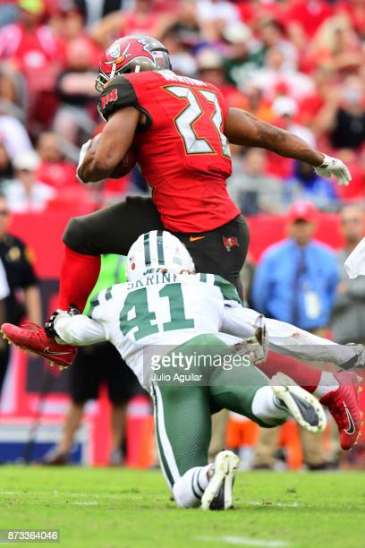 Running back Doug Martin of the Tampa Bay Buccaneers leaps over cornerback Buster Skrine of the New York Jets in the fourth quarter on November 12...