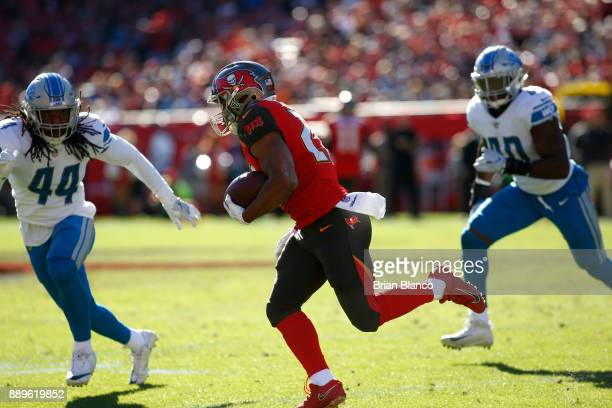 Running back Doug Martin of the Tampa Bay Buccaneers looks to get around linebacker Jalen Reeves-Maybin of the Detroit Lions during a carry in the...