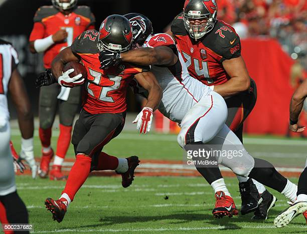 Running back Doug Martin of the Tampa Bay Buccaneers runs the ball as defensive tackle Ra'Shede Hageman of the Atlanta Falcons grabs his face mask in...
