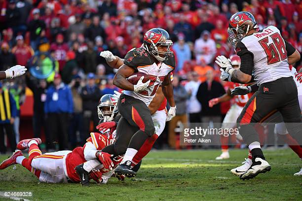 Running back Doug Martin of the Tampa Bay Buccaneers rushes through the tackle attempt of cornerback Kenneth Acker of the Kansas City Chiefs at...