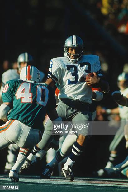 Running back Duane Thomas of the Dallas Cowboys runs with the ball as Dick Anderson of the Miami Dolphins tries to tackle him during Super Bowl VI at...
