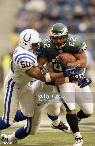 Running back Duce Staley of the Philadelphia Eagles is tackled by David Thornton of the Indianapolis Colts at Veterans Stadium on November 10 2002 in...
