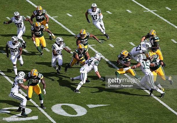Running back DuJuan Harris of the Green Bay Packers returns the opening kick-off before being tackled by linebacker Nick Bellore of the New York Jets...