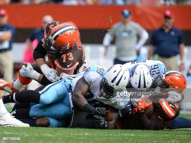 Running back Duke Johnson Jr #29 of the Cleveland Browns is tackled by cornerback Logan Ryan and linebacker Brian Orakpo of the Tennessee Titans as...