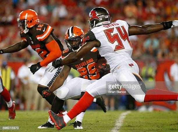 running back Duke Johnson of the Cleveland Browns gets pressure from outside linebacker Lavonte David of the Tampa Bay Buccaneers as during a carry...