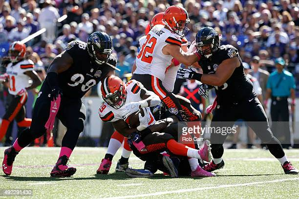 Running back Duke Johnson of the Cleveland Browns is tackled by free safety Kendrick Lewis of the Baltimore Ravens while nose tackle Brandon Williams...