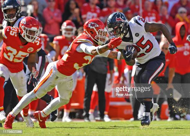Running back Duke Johnson of the Houston Texans rushes up field against pressure from strong safety Tyrann Mathieu of the Kansas City Chiefs during...