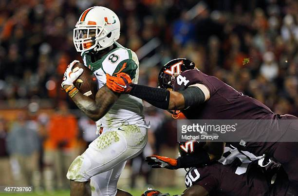 Running back Duke Johnson of the Miami Hurricanes breaks the attempted tackle of defensive end Ken Ekanem of the Virginia Tech Hokies in the first...
