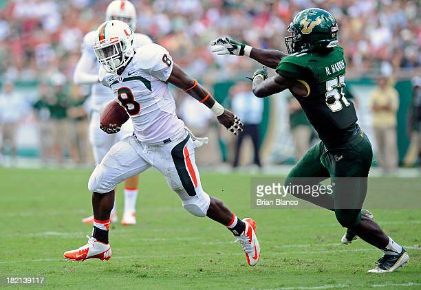 Running back Duke Johnson of the Miami Hurricanes evades linebacker Nigel Harris of the South Florida Bulls during a carry in the first quarter on...