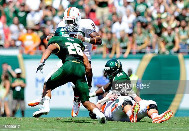 Running back Duke Johnson of the Miami Hurricanes runs for several yards against safety Mark Joyce of the South Florida Bulls on September 28 2013 at...