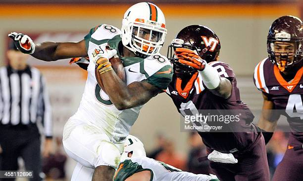 Running back Duke Johnson of the Miami Hurricanes tries to avoid the tackle of safety Detrick Bonner of the Virginia Tech Hokies in the first half at...
