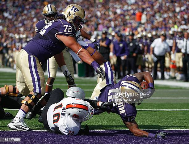 Running back Dwayne Washington of the Washington Huskies crosses the goal line for a touchdown with the help of lineman Micah Hatchie against Taison...
