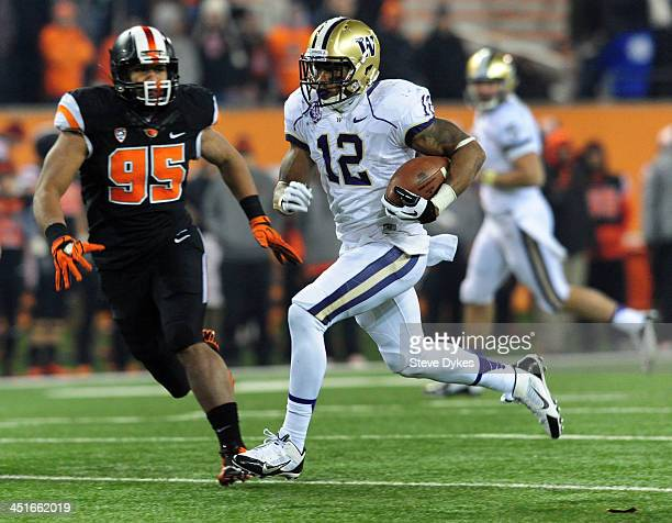 Running back Dwayne Washington of the Washington Huskies heads for the end zone and a touchdown as defensive end Scott Crichton of the Oregon State...