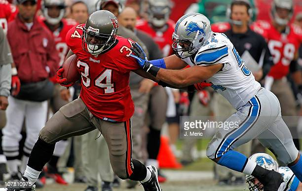 Running back Earnest Graham of the Tampa Bay Buccaneers runs through the tackle of linebacker Bobby Carpenter of the Detroit Lions during the game at...