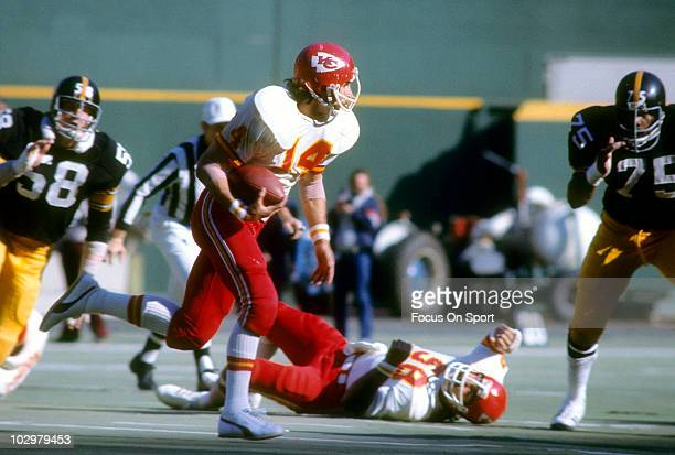 Running Back Ed Podolak of the Kansas City Chiefs running with the ball looks to get pass defensive tackle Joe Greene of the Pittsburgh Steelers...