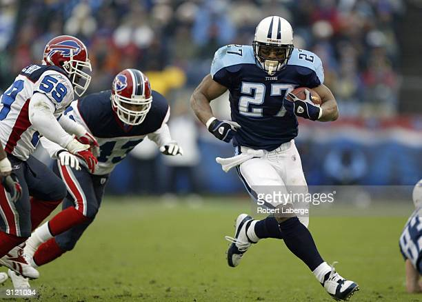 Running back Eddie George of the Tennessee Titans carries the ball against the Buffalo Bills during the game at The Coliseum on December 14 2003 in...