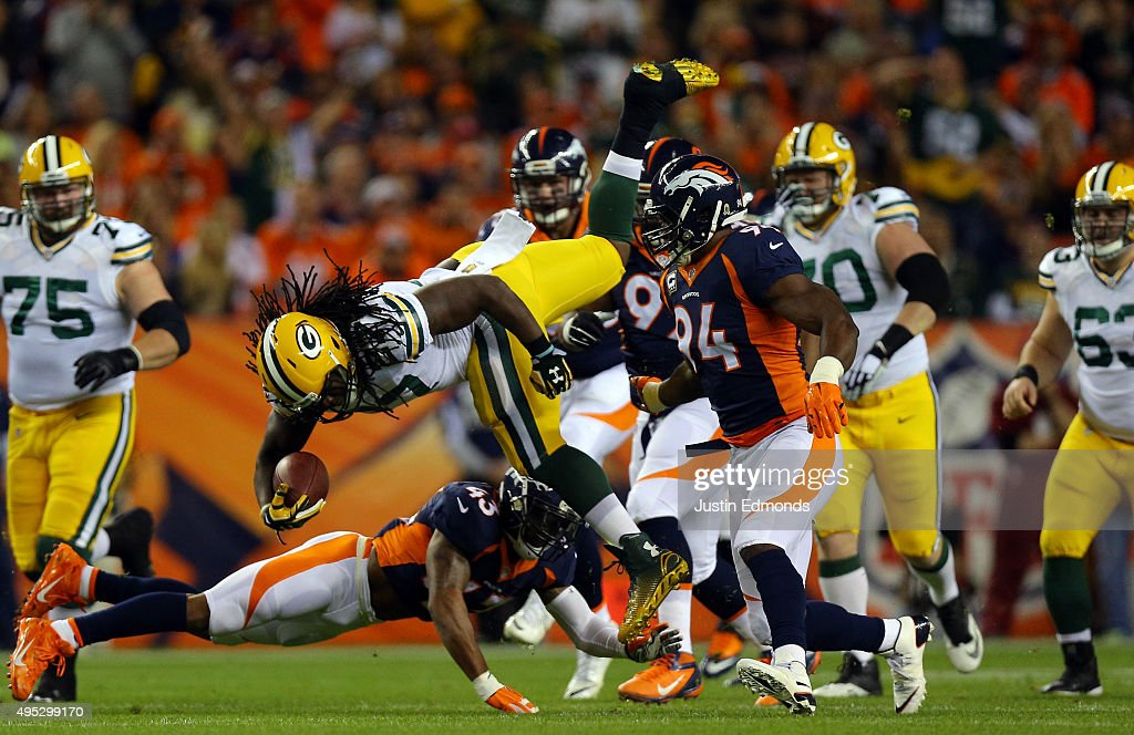 Running back Eddie Lacy #27 is upended after an 11-yard gain by T.J. Ward #43 of the Denver Broncos for a first down in the first quarter at Sports Authority Field at Mile High on November 1, 2015 in Denver, Colorado.