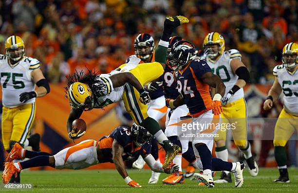 Running back Eddie Lacy is upended after an 11yard gain by TJ Ward of the Denver Broncos for a first down in the first quarter at Sports Authority...