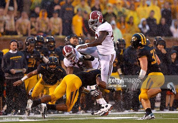 Running back Eddie Lacy of the Alabama Crimson Tide leaps over defenders as he carries the ball upfield during the game against the Missouri Tigers...