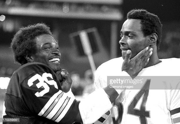 Running back Eddie Payton of the Cleveland Browns meets with his brother Walter Payton of the Chicago Bears following a preseason game on August 25...