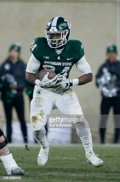 Running back Elijah Collins of the Michigan State Spartans carries the ball against the Rutgers Scarlet Knights during the first half at Spartan...
