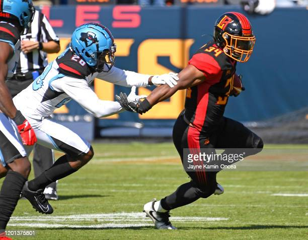 Running back Elijah Hood of the Los Angeles Wildcats runs for a short gain before he is stopped by cornerback Josh Hawkins of the Dallas Renegades in...