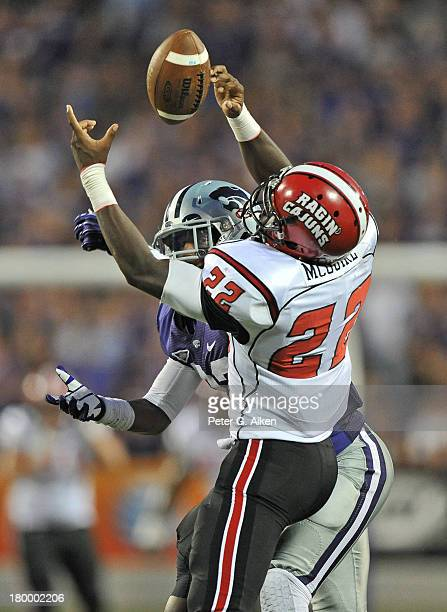 Running back Elijah McGuire of the Louisiana Lafayette Ragin Cajuns reaches out for a pass against linebacker Charmeachelle Moore of the Kansas State...