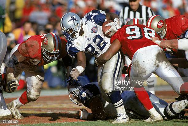 Running back Emmitt Smith of the Dallas Cowboys battles for yards as he gets taken down by the San Francisco 49ers defense during the 1994 NFC...