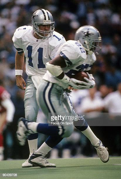 Running Back Emmitt Smith of the Dallas Cowboys in action takes the hand off from quarterback Wade Wilson against the San Francisco 49ers November 12...