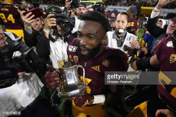 Running back Eno Benjamin of the Arizona State Sun Devils celebrates with the Territorial Cup following the NCAAF game against the Arizona Wildcats...