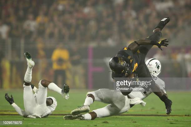 Running back Eno Benjamin of the Arizona State Sun Devils is tackled by linebacker Antjuan Simmons of the Michigan State Spartans during the first...