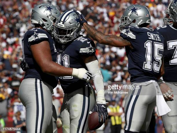 Running back Ezekiel Elliott of the Dallas Cowboys celebrates with teammates after crossing the goal line for a touchdown during second half action...