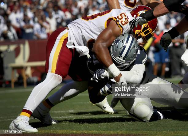 Running back Ezekiel Elliott of the Dallas Cowboys crosses the goal line for a touchdown as linebacker Jon Bostic of the Washington Redskins tries to...