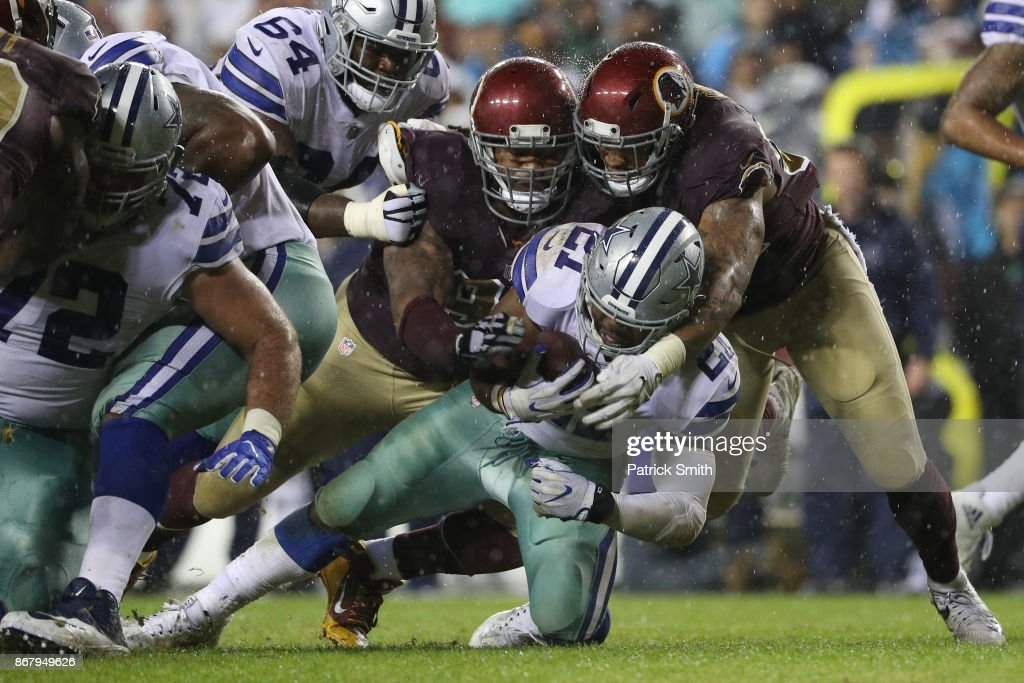 Running back Ezekiel Elliott #21 of the Dallas Cowboys is hit by the Washington Redskins during the fourth quarter at FedEx Field on October 29, 2017 in Landover, Maryland.