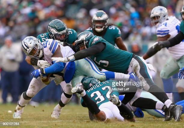 Running back Ezekiel Elliott of the Dallas Cowboys is tackled by cornerback Rasul Douglas defensive end Vinny Curry and outside linebacker Najee...